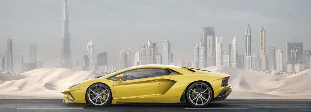 2020 Lamborghini Aventador S yellow exterior driver side driving city skyline in background snow drifts on side of road
