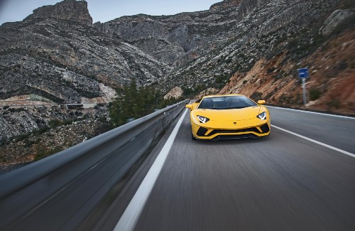2020 Lamborghini Aventador S yellow exterior front driving surrounded by mountains