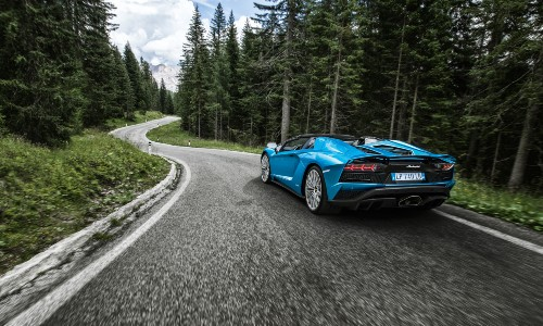 2020 Lamborghini Aventador S Roadster blue driving on curved road through forest
