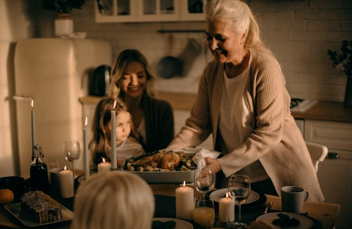 grandma mom and daughter sitting at thanksgiving dinner table