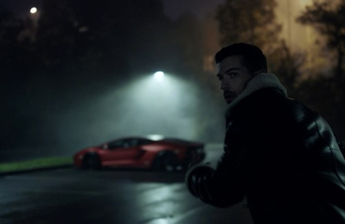 man leaning on fence at night lamborghini in background parked in parking lot