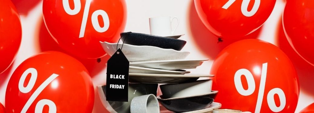 red percent balloons surrounding stack of plates with black friday tag