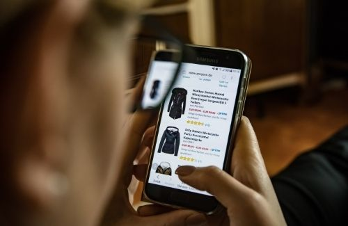 woman shopping online for jackets on smartphone