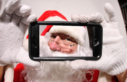 Santa smiling through camera of smartphone screen