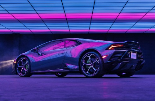 Lamborghini Huracan EVO RWD driver side rear parked under pink and blue lighting