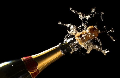 close up of champagne bottle popping open