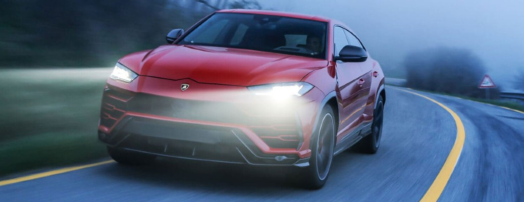 2020 Lamborghini Urus red exterior front fascia driving around curve foggy