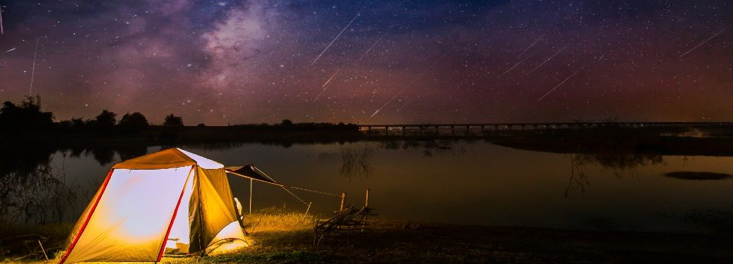 tent set up near lake at night during meteor shower