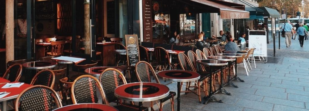 round tables with chairs lined up outside of restaurant