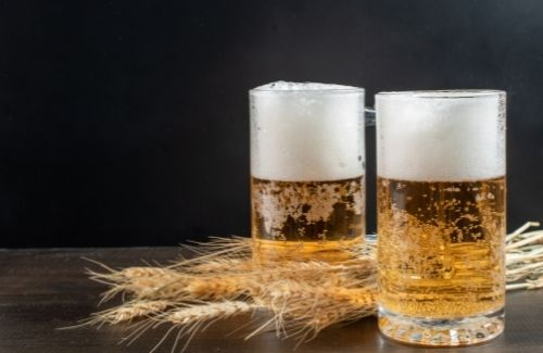two glasses of beer on wooden table with piece of wheat