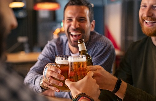 three men in a bar smiling and clinking beers together