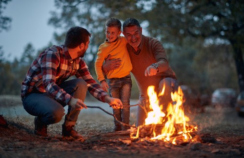 grandfather father and son roasting food over fire at campsite