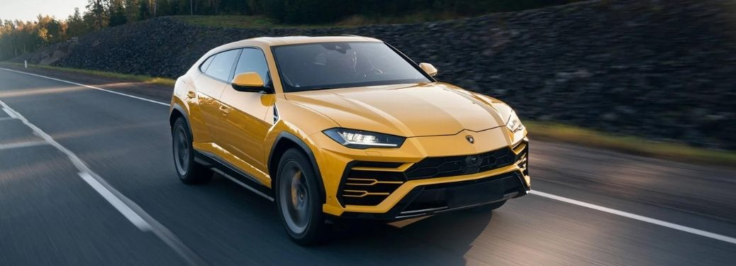 2021 Lamborghini Urus Front Right-Quarter View Driving on a Countryside Road.