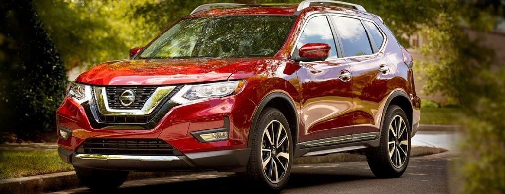 Front view of red 2019 Nissan Rogue driving through woods
