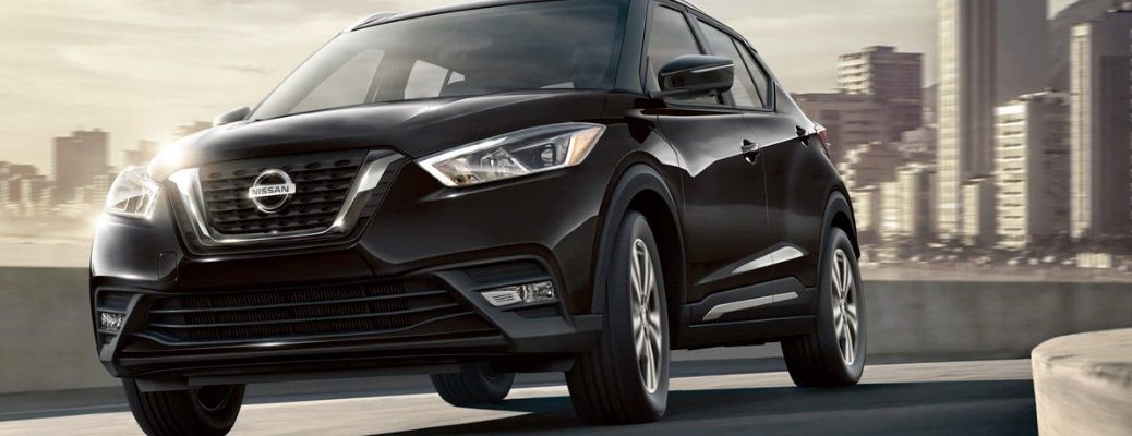 Black 2019 Nissan Kicks driving on city street with skyline in background