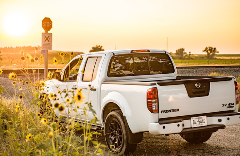 Rear shot of white 2019 Nissan Frontier parked against sunset