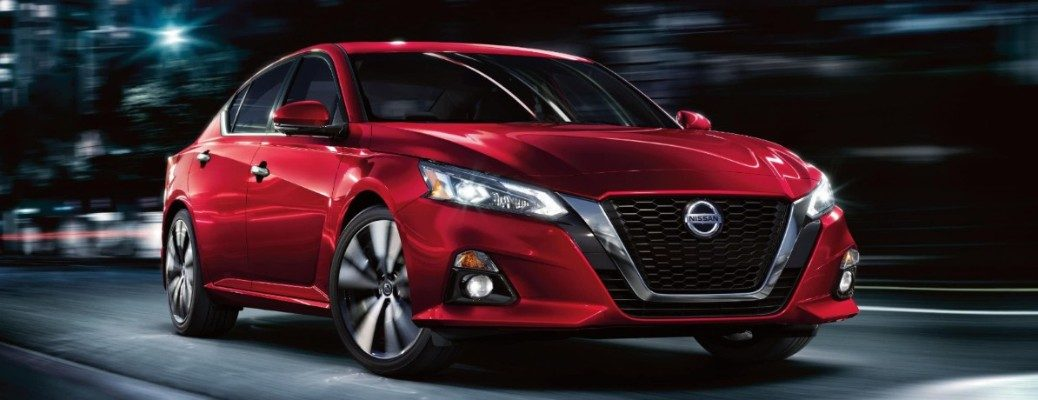 Front view of red 2020 Nissan Altima driving on dark city road