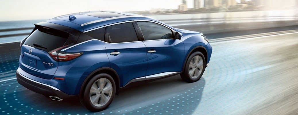 Blue 2019 Nissan Murano driving with city skyline in background