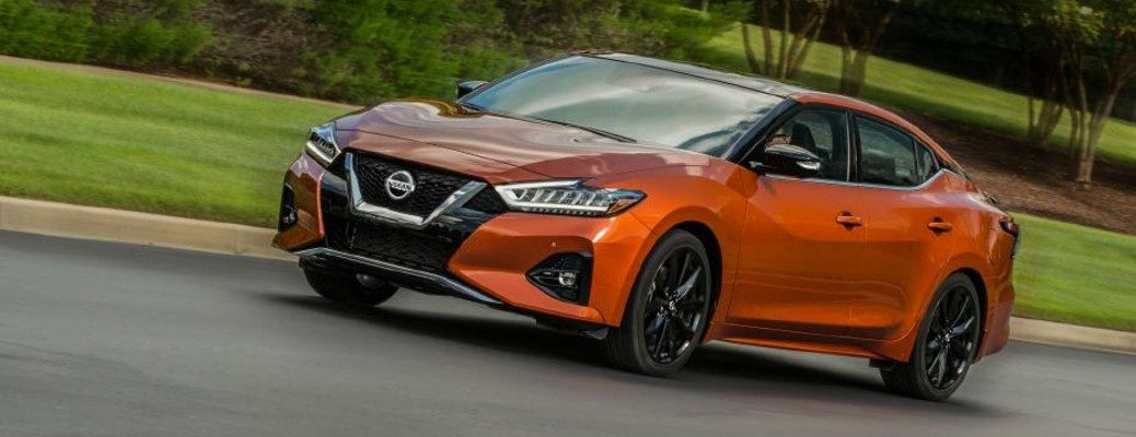 Angled view of orange 2020 Nissan Maxima driving on residential road