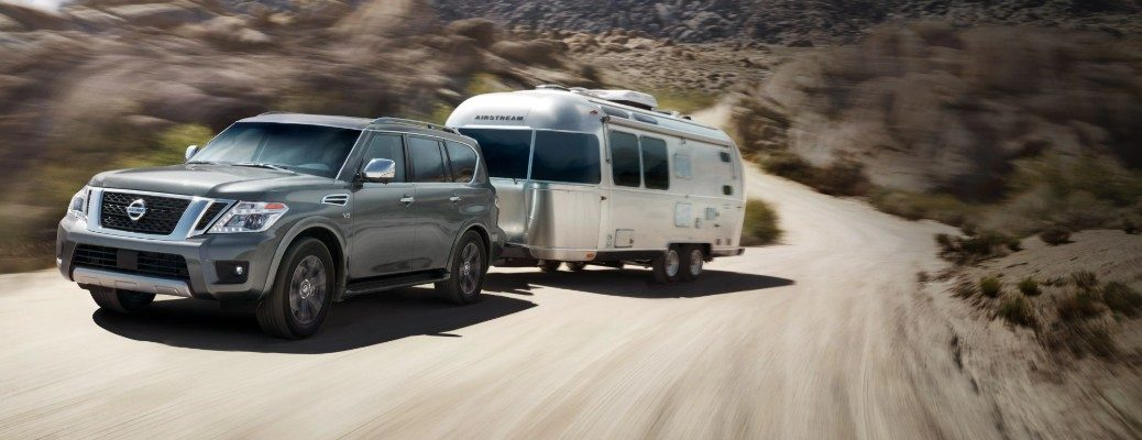 2020 Nissan Armada towing trailer on dirt road