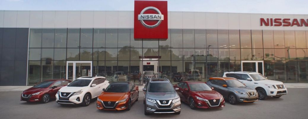 Image of Nissan models parked in front of a Nissan dealership