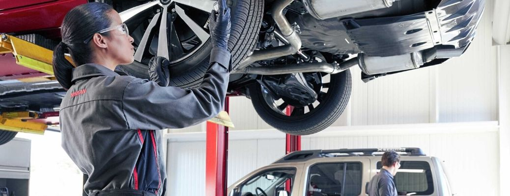 Image of a Nissan service tech inspecting a Nissan vehicle's tires