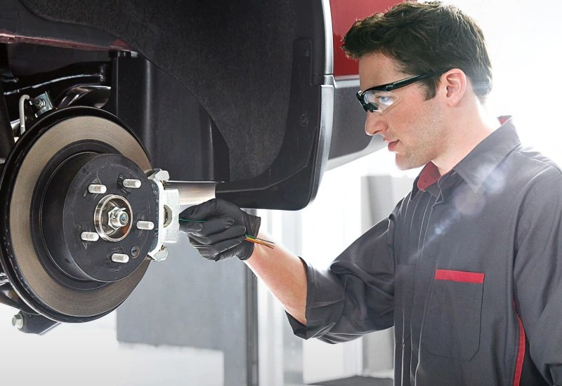 Image of a Nissan service tech checking a Nissan vehicle's brakes