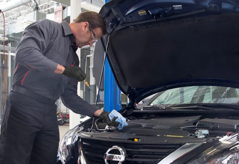 Image of a Nissan service tech changing a Nissan vehicle's oil