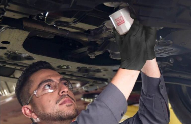 Image of a service technician replacing the oil filter on a Nissan vehicle