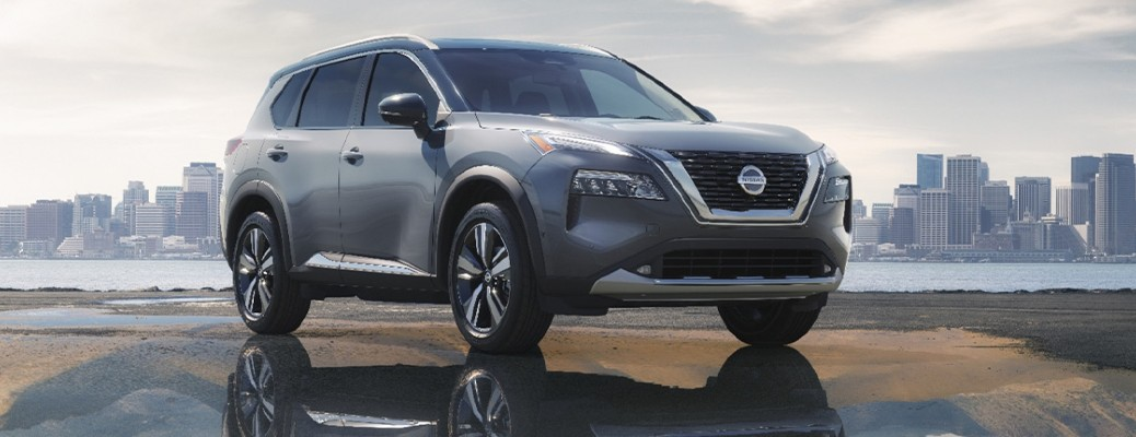 2021 Nissan Rogue parked in a puddle with a city landscape in the background