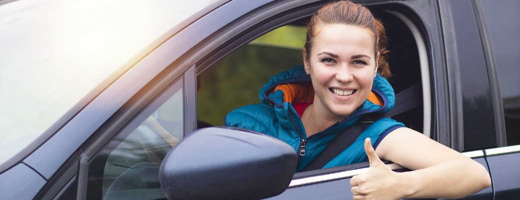 Woman smiling while sticking her head out of a car window with her thumb up.