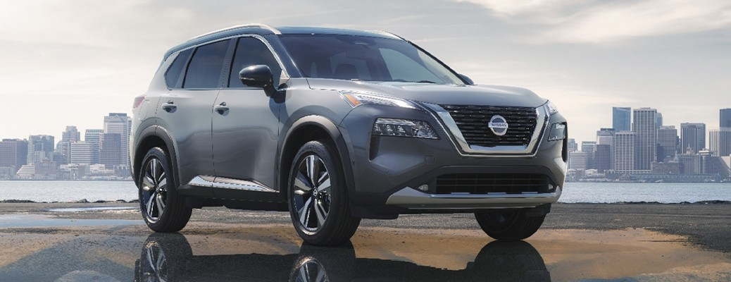 A 2021 Nissan Rogue parked near a body of water with a city landscape in the background