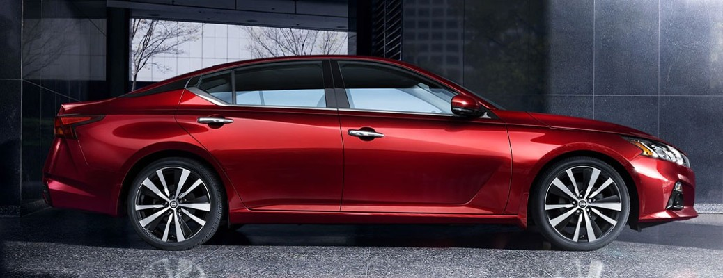 A red-colored 2021 Nissan Altima parked in a covered structure