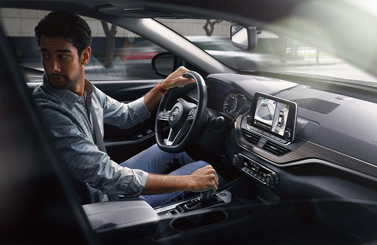 A man looking out the rear window while operating a 2021 Nissan Altima