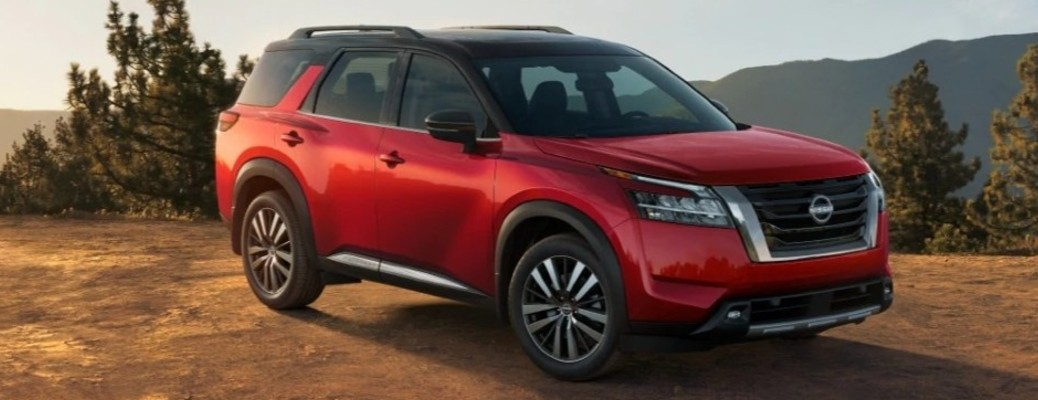 A red-colored 2022 Nissan Pathfinder parked outside