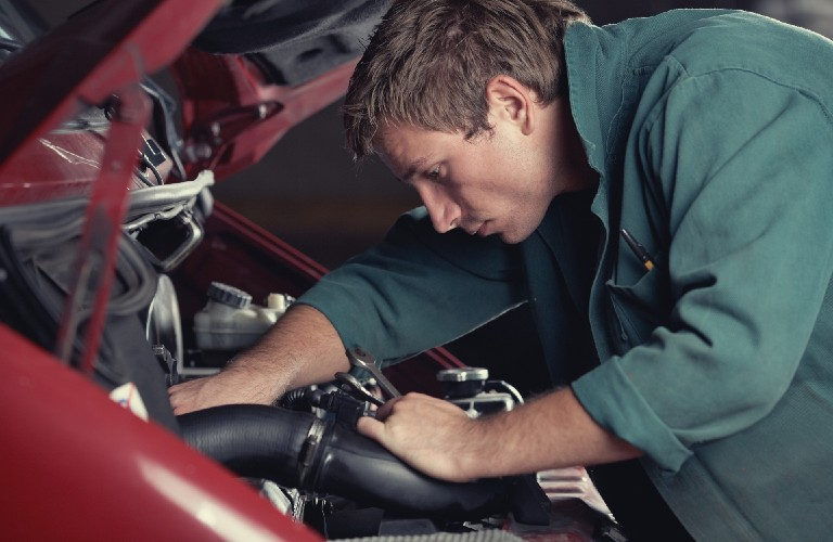 A man working under the hood of a red-colored vehicle