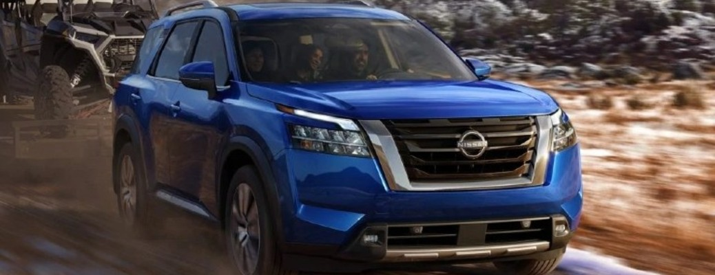 A blue-colored 2022 Nissan Pathfinder driving outside