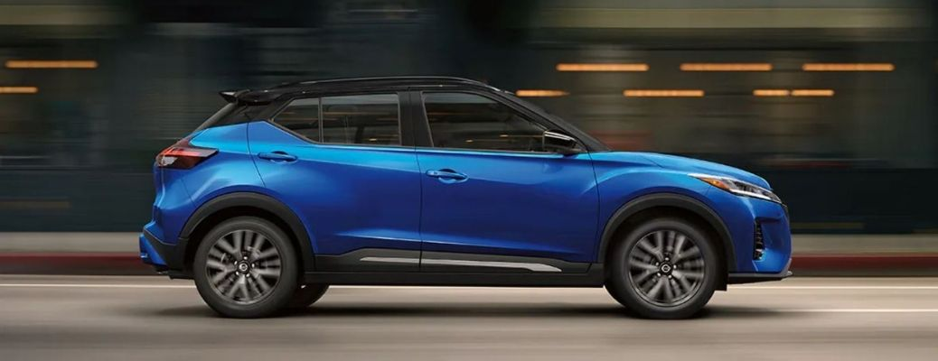 Side view of a blue-colored 2021 Nissan Kicks driving swiftly on the streets