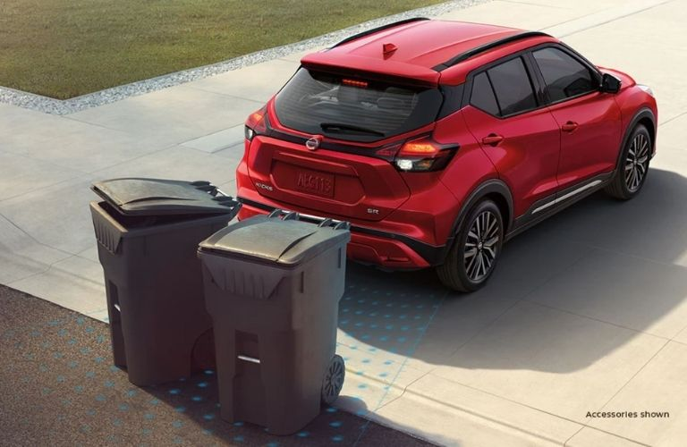 Rear view of a red-colored 2021 Nissan Kicks with garbage cans behind it