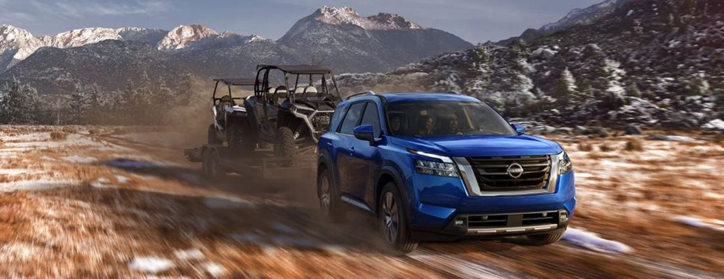 A blue-colored 2022 Nissan Pathfinder towing two ATVs on a trailer trailer on a snow and grass with mountains in the background