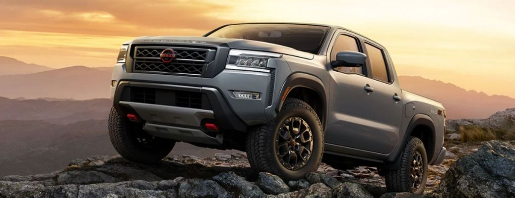 A gray 2022 Nissan Frontier pickup climbing a rocky cliff at sunset