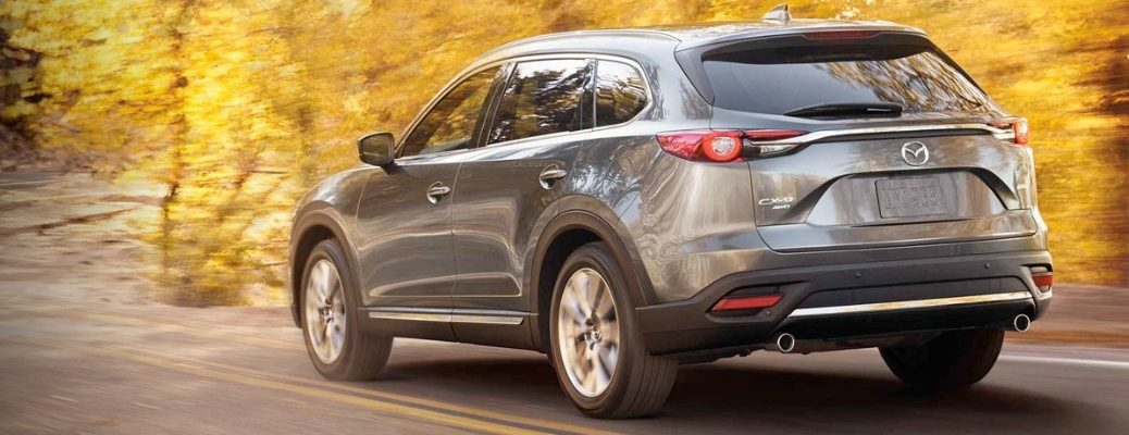 Rear view of 2019 Mazda CX-9 driving on tree-lined country road