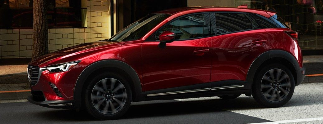 Profile view of red 2019 Mazda CX-3 on city curb
