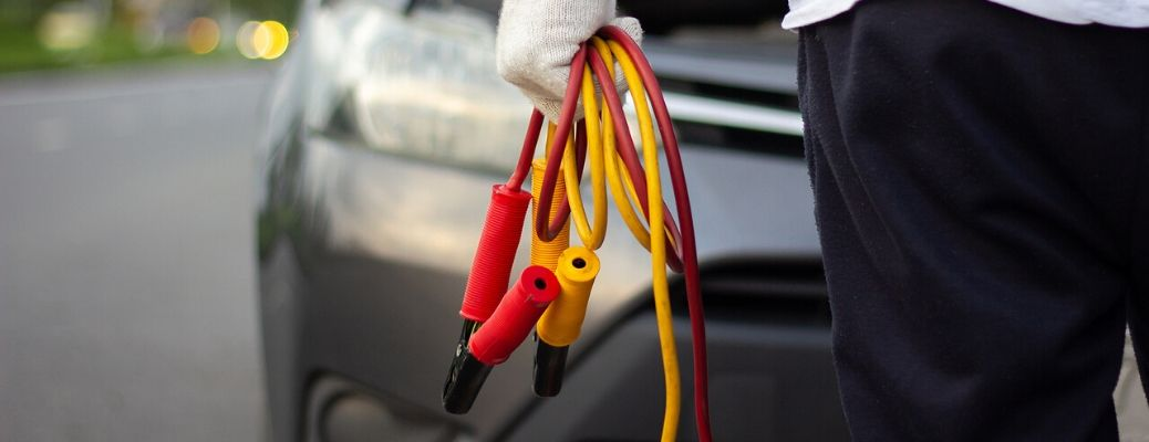 Image of someone carrying jumper cables towards a car