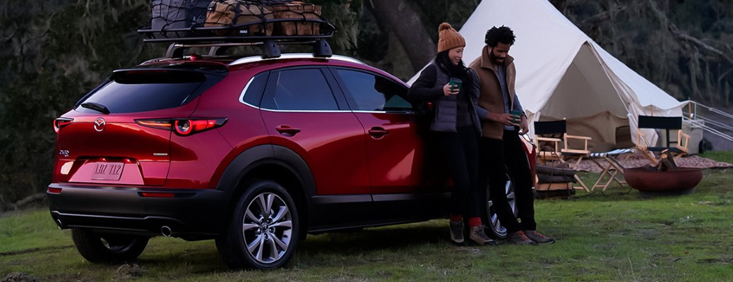 2021 Mazda CX-30 parked on grass with a man and woman leaning on it and a white tent pitched in the background
