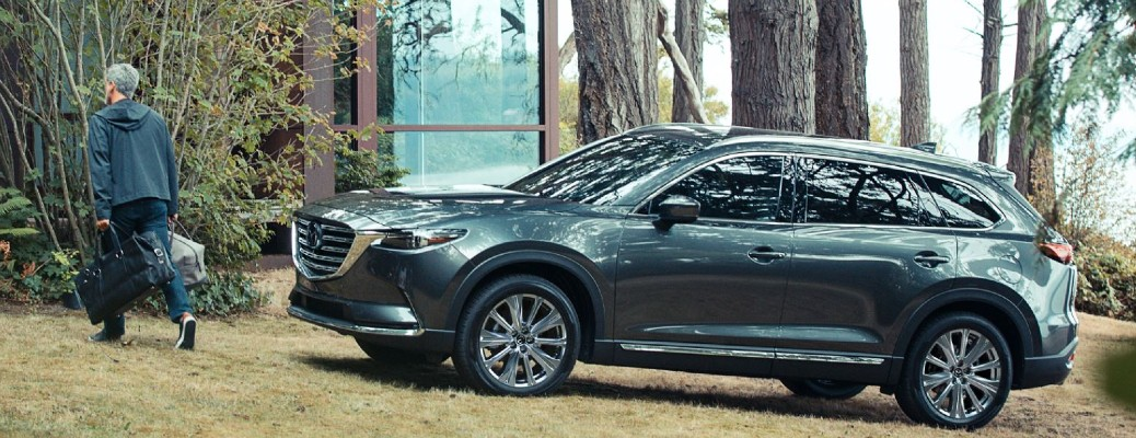 Man walking away from 2021 Mazda CX-9 with luggage in his hands. The vehicle is parked in a wooded area
