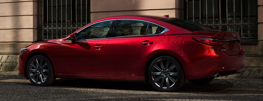 A red-colored 2021 Mazda6 parked outside on the side of a street.