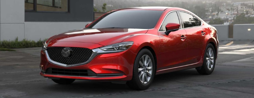 A red-colored 2021 Mazda6 driving on a road