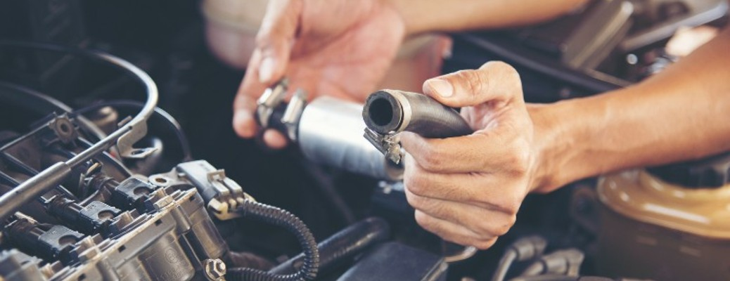 A person holding a part while working on a vehicle under the hood