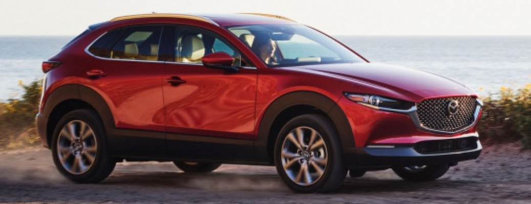 A red-colored 2021 Mazda CX-30 driving outside